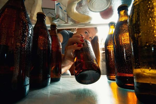 Eine-Frau-blickt-in-einen-Kuehlschrank-der-mit-Bierflaschen-gefu-llt-ist