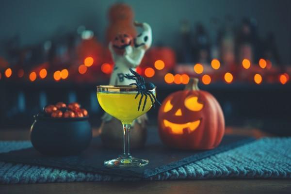 Ein-Halloween-Cocktail-steht-auf-einem-mit-Kuerbis-dekoriertem-Tisch