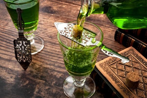 Giftgruene-Fluessigkeit-wird-ueber-einen-Absinth-Loeffel-auf-dem-ein-Stueck-Zucker-liegt-in-ein-Absinth-Glas-gegossen