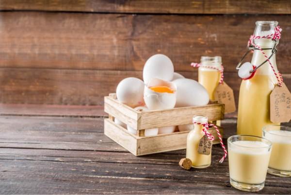 Eierlikoer-in-mehreren-kleinen-Flaschen-daneben-Einer-in-einer-kleinen-Holzkiste