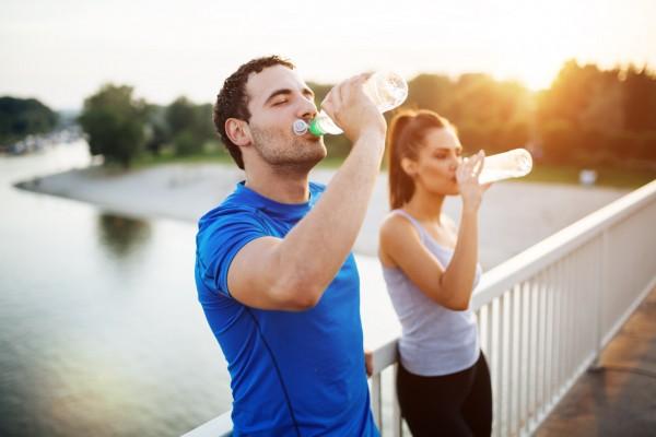 Ein-Mann-und-eine-Frau-in-Sportbekleidung-trinkgen-aus-Wasserflaschen