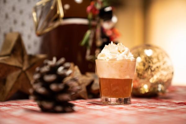 Bratapfellikoer-mit-Sahnehaube-vor-weihnachtlicher-Dekoration