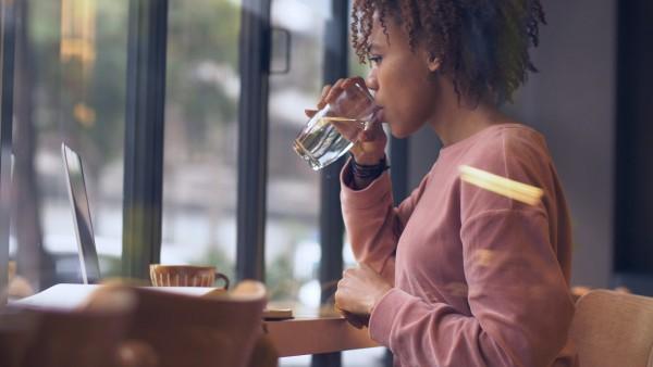 Eine-junge-Frau-trinkt-ein-Glas-Wasser-bei-der-Arbeit