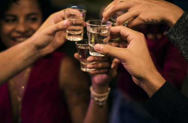 Freunde-stossen-mit-einem-Pinchen-Wodka-an