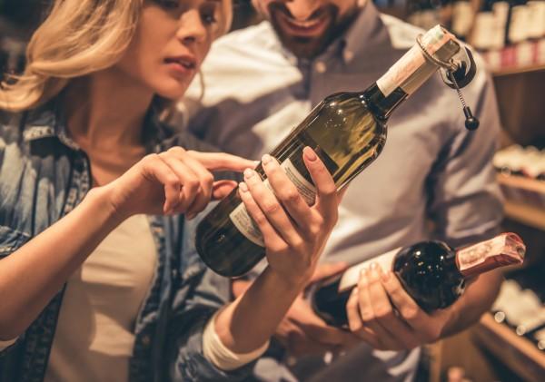 Eine-Frau-zeigt-auf-eine-Flasche-Wein-Im-Hintergrund-haelt-ein-Mann-eine-Flasche-Wein-in-der-Hand