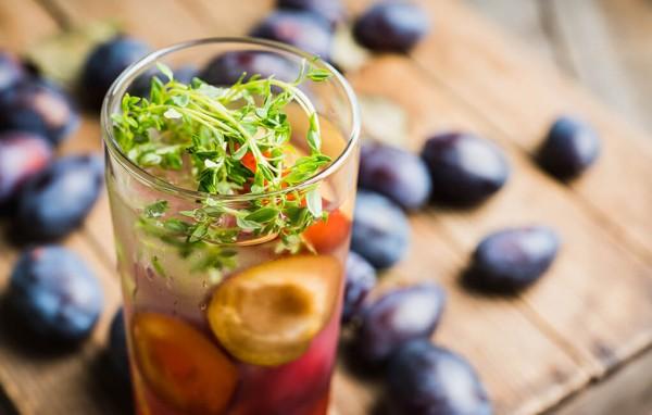 Cocktail-mit-Pflaumen-und-Thymian-auf-rustikalen-Hintergrund